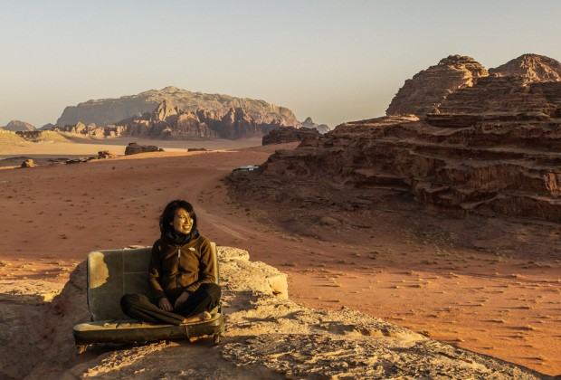 Girl Sitting ATop Bedouin Camp At Sunrise in Wadi Rum, Jordan